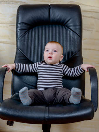 captivated: Fun portrait of a cute chubby little baby boy sitting in a black leather office chair conceptual of his goals and aspirations as a businessman or career