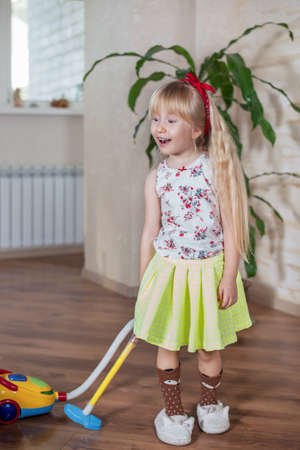 vivacious: Happy pretty little blond girl with a lovely vivacious smile cleaning house with a colorful toy vacuum cleaner, full length portrait