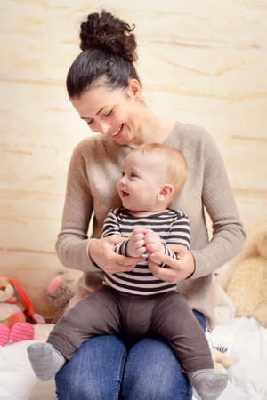 Happy Young Mom and her Cute Baby Boy at Home, Smiling at the Camera Together.