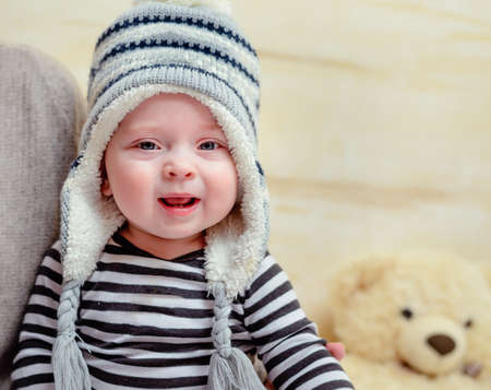 Adorable young baby in a blue and white knitted winter outfit sitting on his mothers lap as she dresses him with matching blue shoes or booties