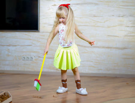 Full Length Shot of a Little Blond Girl Holding Broom, Doing Household Chores Alone Seriously