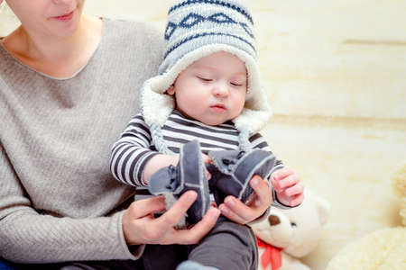 booties: Adorable young baby in a blue and white knitted winter outfit sitting on his mothers lap as she dresses him with matching blue shoes or booties