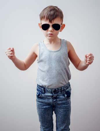 Tough looking serious child in sunglasses, gray shirt and blue jeans making symbols with fingers