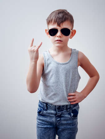defiance: Tough male child in sunglasses, gray shirt and blue jeans with hand on hip making symbols with hand over gray background