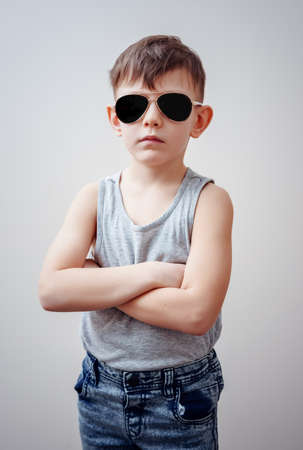 defiance: Cute little single boy in sunglasses, sleeveless shirt and blue jeans with folded arms over gray background Stock Photo