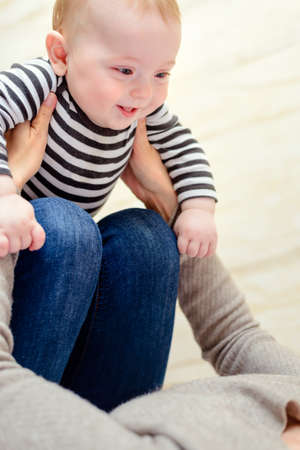 simulate: Close up of laughing happy baby in striped shirt being held in hands and on knees of playful parent Stock Photo