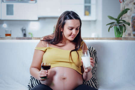make a choice: Front view of grinning pregnant woman holding glass of wine in one hand and milk in the other trying to make a choice while sitting on white sofa