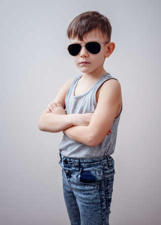 muscle boy: Cute little single boy in sunglasses, sleeveless shirt and blue jeans with folded arms over gray background Stock Photo