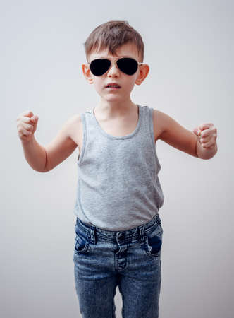 tough: Tough looking serious child in sunglasses, gray shirt and blue jeans making symbols with fingers