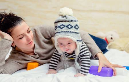 knit cap: Happy young mother laying down in bed with cute baby wearing large knit cap and crawling away from her Stock Photo