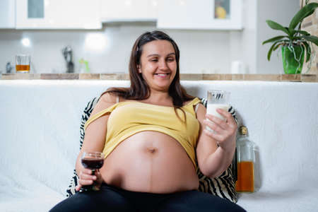 foetus: Smiling young pregnant woman in yellow shirt choosing a glass of milk instead of wine while seated on white sofa Stock Photo