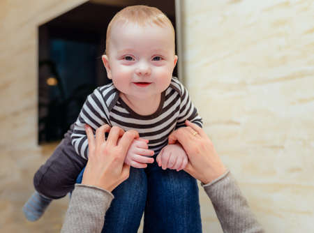 simulate: Giggling baby in striped shirt up on knees of adult who is holding her hands to simulate flying