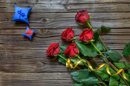 splintered: Old splintered wooden background under a bundle of five stemmed roses and star shaped blue box Stock Photo