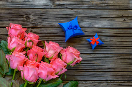tied in: Star shaped blue valentine gift box tied in red bow and pink stemmed roses neatly arranged at bottom corner of wooden table background with copy space