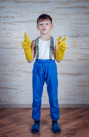 wearing slippers: Single cute smiling little boy wearing blue slippers, pants with suspenders and oversized rubber gloves