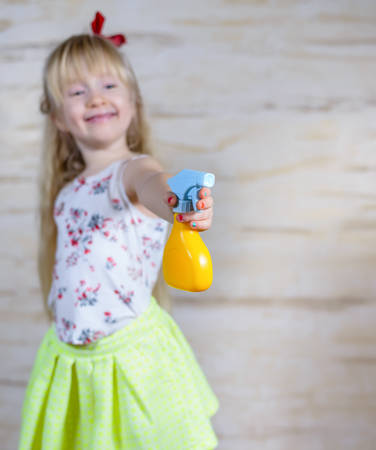 atomiser: Single cute little girl in long blond hair squirting water in the air with yellow and blue spray bottle