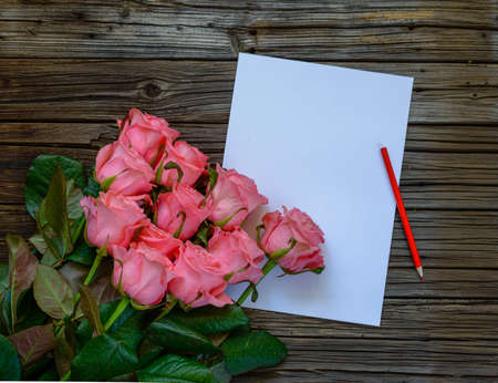 well loved: Dozen pink roses on stems beside plain white paper and red colored pencil on a knotted dark wood table
