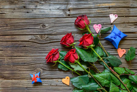 splintered: Worn out splintered wooden background under a five stemmed roses and two star shaped blue gift boxes tied in little strings