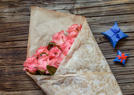 tryst: Wrapped bouquet of pink roses with Valentines gifts for a sweetheart in decorative blue boxes on a rustic wooden table, overhead view Stock Photo
