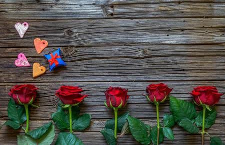 Valentines achtergrond met rode rozen die als grens op een rustieke houten tafel, harten en giften voor een geliefde met een kopie ruimte