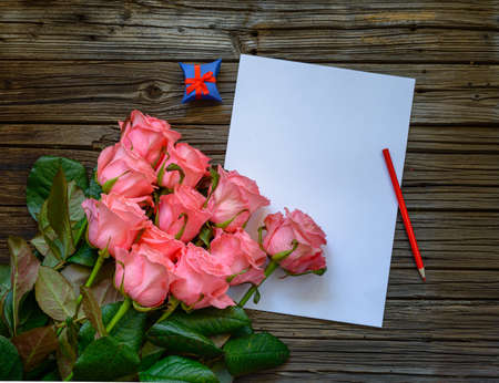 loved: Bouquet of beautiful fresh pink roses with a blank love letter and pencil to write a Valentines message to a loved one with two blue gift boxes alongside