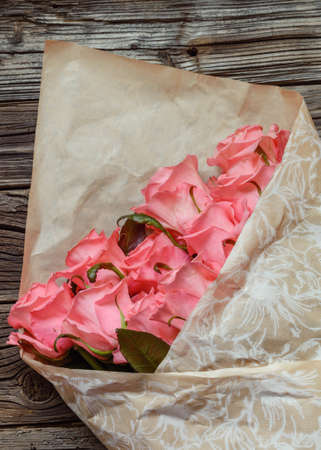 tryst: Bouquet of gift wrapped pink roses symbolic of love, romance, Valentines Day, Mothers Day or anniversary on a rustic wood background with copy space