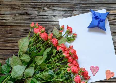 tryst: Single white blank sheet of paper with copy space on table with weathered wooden surface next to bundle of pink roses, heart shapes and little gift box
