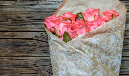 Bouquet of gift wrapped pink roses symbolic of love, romance, Valentines Day, Mothers Day or anniversary on a rustic wood background with copy space