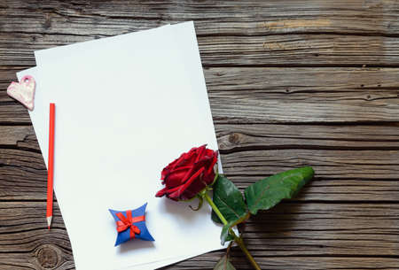 centered: Pair of stacked blank papers centered on table with red rose and little blue gift box