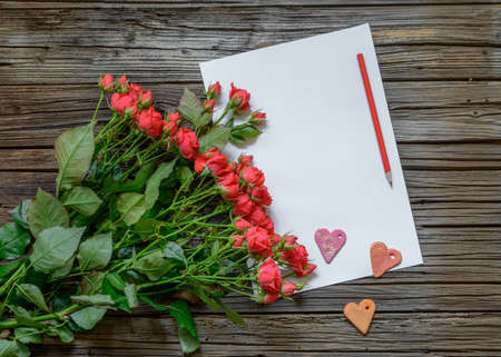 tryst: Blank white paper with copy space on top of wooden surface beside bundle of roses, Valentines Day hearts and pencil
