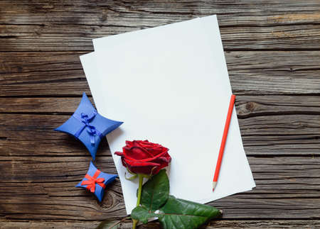 tryst: Pair of stacked blank papers centered on table with red rose and little blue gift box