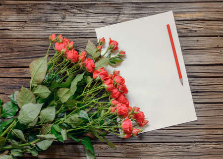 tryst: Blank white paper with copy space on top of weathered wooden surface surrounded by bundle of roses and pencil