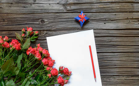 tryst: Blank white paper with copy space on top of weathered wooden surface surrounded by bundle of roses, pair of gift boxes and pencil