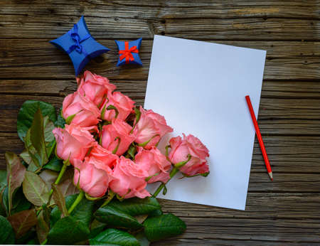 in loved: Bouquet of beautiful fresh pink roses with a blank love letter and pencil to write a Valentines message to a loved one with two blue gift boxes alongside