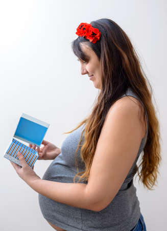 hair band: Single pregnant female in sleeveless gray shirt and red hair band on long brown hair looking down Stock Photo