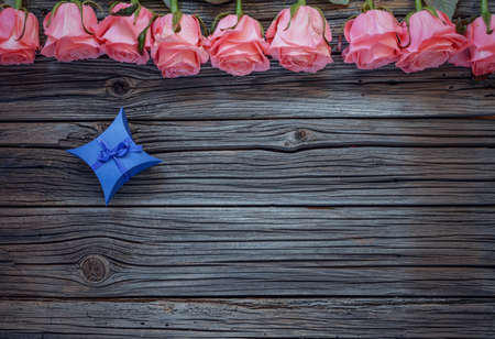 diamond shaped: Tiny blue diamond shaped bowed gift box over worn out wooden background with roses on top Stock Photo