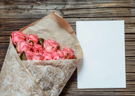 tryst: Brown bag of freshly gathered pink stemmed roses next to blank white paper and colored pencil over weathered wooden background Stock Photo