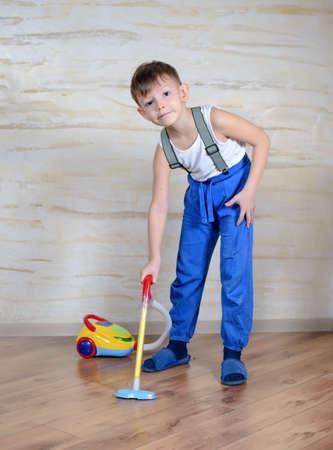 make believe: Cute little boy in blue pants, slippers and suspenders using toy vacuum cleaner on hardwood floor