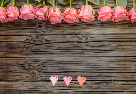tryst: Three little Valentines Day paper heart objects and neatly arranged row of pink roses Stock Photo