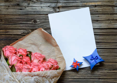 star shaped: Brown bag of multiple pink stemmed roses with blank white paper and blue star shaped gift box over weathered wooden background