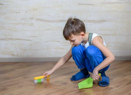 Niño pequeño lindo en pantalones azules, zapatillas y tirantes utilizando pequeña escoba de mano y un recogedor de suelo de madera dura