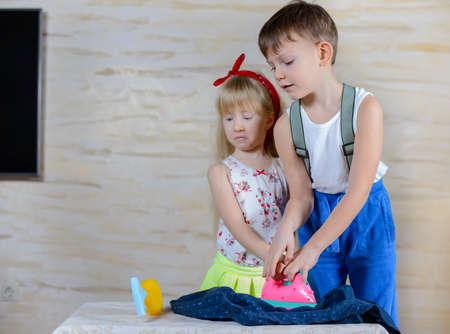 少年と少女は、アイロンをかけている家事を果たしているカラフルなピンクのおもちゃ鉄に保持しようと両方一緒に