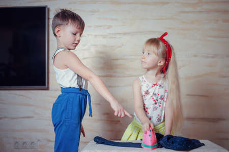 bossy: Bossy boy in blue pants playing husband while pointing at pink toy iron being used to press clothes by little blond girl