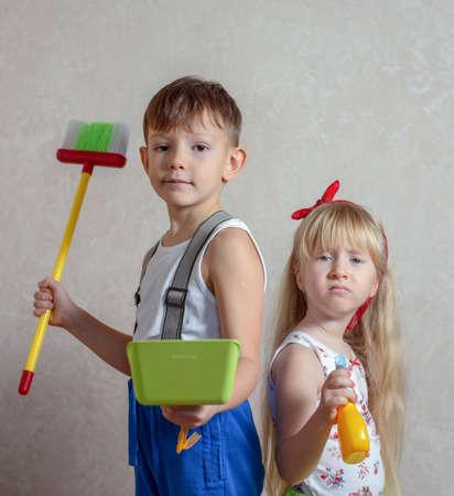 aseo: niña y el hierro que sostiene a muchacho y la escoba con el ceño fruncido expresión de malestar por haber sido obligado a hacer las tareas del hogar Foto de archivo