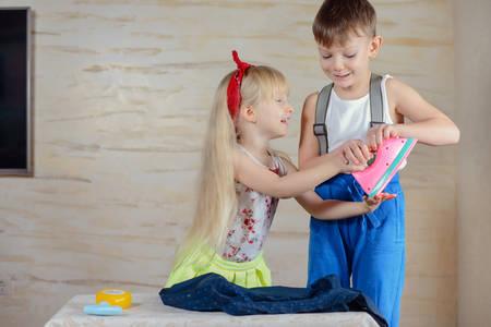 男の子と女の子のモックの家で洗濯とカラフルなピンクのプラスチックのおもちゃ鉄争いを笑ってください。