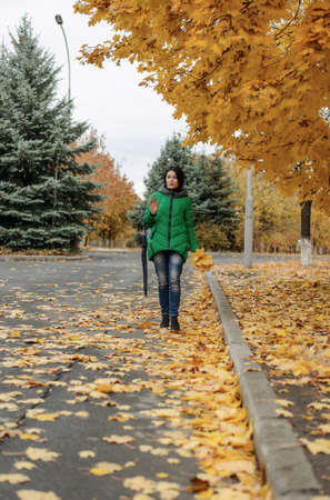 approaching: Beautiful single carefree woman in winter coat, jeans and closed umbrella walking along sidewalk covered with leaves