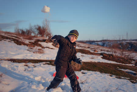 tossing: Small boy tossing a snowball at the camera as he plays outdoors in a snowy winter field