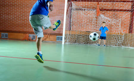 goalie: Close up low angle view from behind of a young boy kicking a soccer ball for goal with another small boy playing goalie Stock Photo