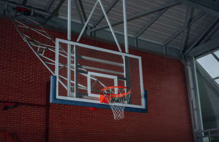 backboard: Basketball equipment on an indoor court with a view from below of the hoop, net and backboard on the goalpost