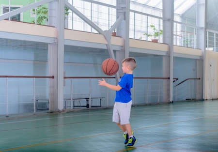 Young boy playing basketball on a bright indoor court with large windows preparing to catch the ball mid air